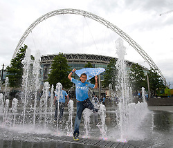 © licensed to London News Pictures. 14/05/2011. London, UK. A young Manchester City fan celebrate runs through a fountain outside Wembley Stadium today (14/05/2011) after seeing their team win the FA Cup for the 5th time against Stoke City. Photo credit should read Ben Cawthra/LNP