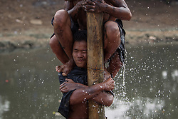 August 17, 2017 - Central Jakarta, Jakarta, Indonesia - Indonesian men react as they hold on to a greased pole during the ''Panjat Pinang'' competition in order to get to the prizes tied to the top during celebrations for the 72nd Indonesia National Independence day on August 17, 2017 in Jakarta, Indonesia. Indonesia became an independent nation on 17th August 1945, having previously been under Dutch rule. (Credit Image: © Afriadi Hikmal via ZUMA Wire)