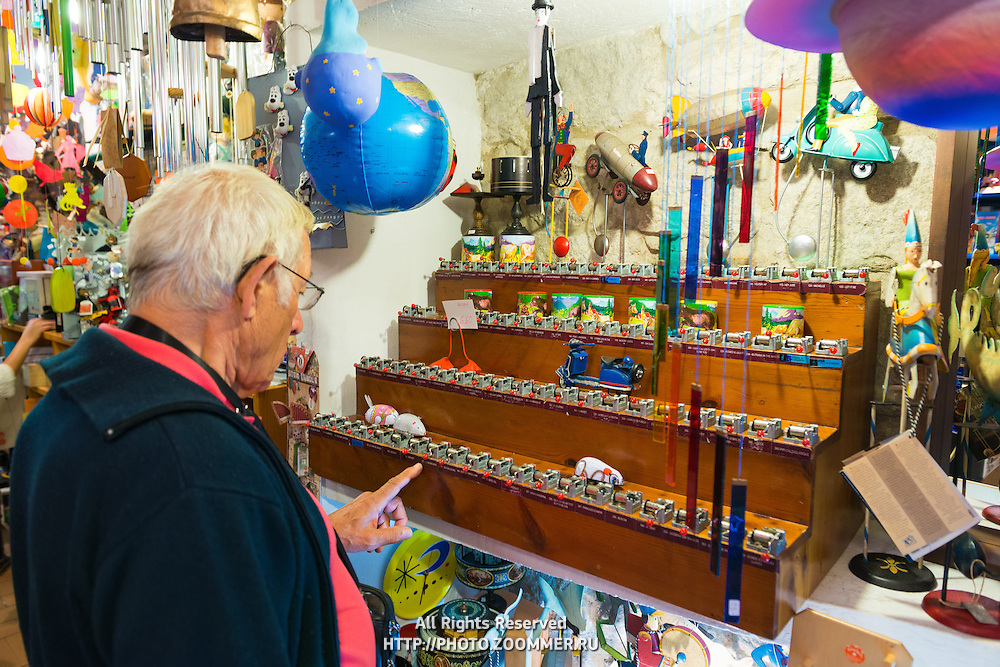 Old man play music box in La Carpa, vintage-style retro toy shop in Spain