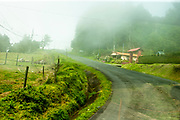 Curvy rural road in Costa Rica with green foliage and fog. On the way to Poas Volcano.
