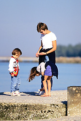 Mother & Daughters Looking For Shells