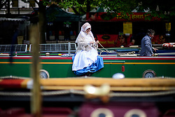 © Licensed to London News Pictures.30/04/2017.London, UK. A woman dressed in period costume sits on the side of a narrowcast as the Canalway Cavalcade festival takes place in Little Venice, London on Saturday, 30 April 2017. Inland Waterways Association's annual gathering of canal boats brings around 130 decorated boats together in Little Venice's canals on May bank holiday weekend. Photo credit: Ben Cawthra/LNP