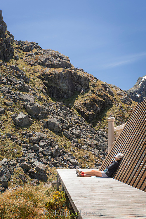Hiker resting at the Harris Saddle Shelter, Routeburn Track, South Island, New Zealand