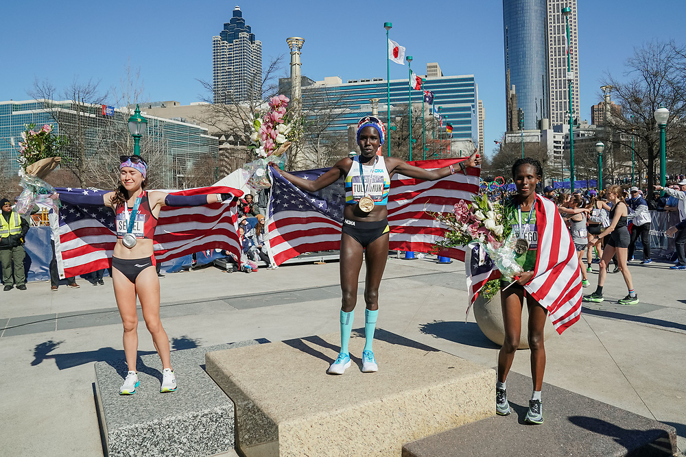 Aliphine Tuliamuk (center), Molly Seidel (left) and Sally Kipyego (right) celebrate winning first, second, and third, respectively, during the 2020 U.S. Olympic marathon trials in Atlanta on Saturday, Feb. 20, 2020. Photo by Kevin D. Liles for The New York Times
