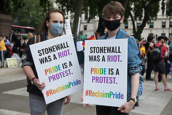 Two LGBTI+ protesters pose in Parliament Square holding placards before the first-ever Reclaim Pride march on 24th July 2021 in London, United Kingdom. Reclaim Pride replaced the traditional Pride in London march, which many feel has become too commercial and strayed from its roots in protest, and was billed as a People's Pride march for LGBTI+ liberation. Campaigners called for the banning of LGBTI+ conversion therapy, the reform of the Gender Recognition Act, the provision of a safe haven for LGBTI+ refugees and for LGBTI+ people to be decriminalised worldwide and marched in solidarity with Black Lives Matter.