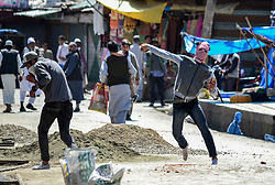 April 27, 2018 - Srinagar, J&K, India - A Kashmiri protester throw stones towards Indian government forces during clashes after the friday prayers outside the Grand mosque or Jamia Masjid in Srinagar, Indian administered Kashmir. Clashes erupted between Kashmiri protesters and Indian paramilitary forces after Friday congregation prayers near Kashmir's historic Grand Mosque or Jamia Masjid in old city of Srinagar. The stone throwing protesters were protesting against Indian rule. (Credit Image: © Saqib Majeed/SOPA Images via ZUMA Wire)