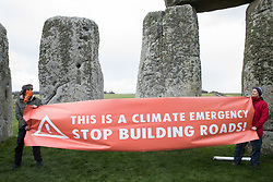 Climate activists hold a banner calling for an end to new road building during a Mass Trespass at Stonehenge on 5th December 2020 in Salisbury, United Kingdom. The trespass was organised in protest against the approval by Transport Secretary Grant Shapps of a £1.7bn project for a two-mile tunnel beneath the World Heritage Site and a further eight miles of dual carriageway for the A303, as well as the government's £27bn Road Investment Strategy 2 (RIS2).