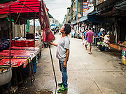21 SEPTEMBER 2016 - BANGKOK, THAILAND: A street vendor sets up an umbrella in the street market next to what used to be the Bang Chak Market. The market closed permanently on January 4, 2016. The Bang Chak Market served the community around Sois 91-97 on Sukhumvit Road in the Bangkok suburbs. Bangkok city authorities put up notices in late November 2015 that the market would be closed by January 1, 2016 and redevelopment would start shortly after that. Market vendors said condominiums are being built on the land.      PHOTO BY JACK KURTZ