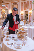 A smarlty dressed male waiter pours tea in Palm Court at The Ritz on the 4th October 2019 in London in the United Kingdom. Palm Court is a glass-ceilinged venue for extravagant afternoon tea at the 5 star The Ritz hotel.