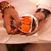 An Indian bridegroom holds a thread, two marigolds, and a fifty rupee note during a Hindu wedding in Delhi. The other side of the thread is held by the bride on his right hand side. As a part of the ceremony, they will later stretch the thread until it tears.