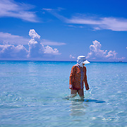 An asian tourist protects herself from the dangers of the sun in the ocean at White Beach,  Boracay Island, the Philippines on October 5, 2008, Photo Tim Clayton..Asian tourists at White Beach, Boracay Island, the Philippines...The 4 km stretch of White beach on Boracay Island, the Philippines has been honoured as the best leisure destination in Asia beating popular destinations such as Bali in Indonesia and Sanya in China in a recent survey conducted by an International Travel Magazine with 2.2 million viewers taking part in the online poll...Last year, close to 600,000 visitors visited Boracay with South Korea providing 128,909 visitors followed by Japan, 35,294, USA, 13,362 and China 12,720...A popular destination for South Korean divers and honeymooners, Boracay is now attracting crowds of tourists from mainland China who are arriving in ever increasing numbers. In Asia, China has already overtaken Japan to become the largest source of outland travelers...Boracay's main attraction is 4 km of pristine powder fine white sand and the crystal clear azure water making it a popular destination for Scuba diving with nearly 20 dive centers along White beach. The stretch of shady palm trees separate the beach from the line of hotels, restaurants, bars and cafes. It's pulsating nightlife with the friendly locals make it increasingly popular with the asian tourists...The Boracay sailing boats provide endless tourist entertainment, particularly during the amazing sunsets when the silhouetted sails provide picture postcard scenes along the shoreline...Boracay Island is situated an hours flight from Manila and it's close proximity to South Korea, China, Taiwan and Japan means it is a growing destination for Asian tourists... By 2010, the island of Boracay expects to have 1,000,000 visitors.