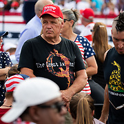 """WINSTON-SALEM, NC - SEPT 8: A man with a QANON shirt, a right wing conspiracy group, stands next to a man with a mohawk and """"Don't Tread On Me Shirt"""" as supporters of President Donald Trump wait for the incumbent before he's to appear at a campaign rally at Smith Reynolds Regional Airport in Winston-Salem, NC on September 8, 2020. North Carolina will be a battle ground state in the 2020 presidential election.  (Photo by Logan Cyrus for Bloomberg)"""