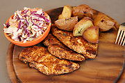 Broiled chicken breast on wooden platter with baked potatoes and coleslaw salad