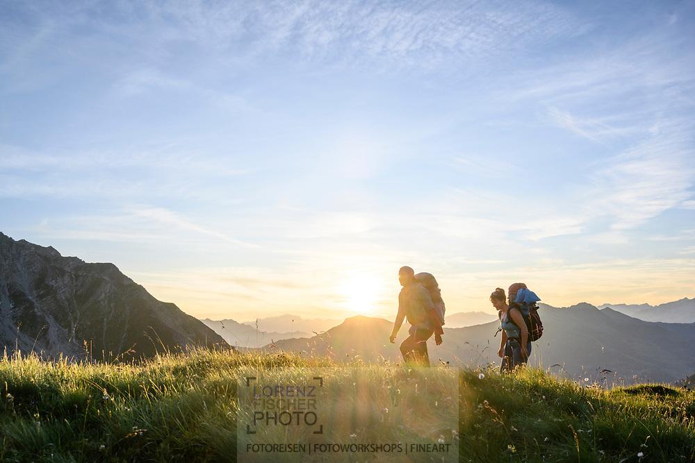 Zwei Wanderer oberhalb der Alp Sanaspans auf einer Wanderung von der Alp Sanaspans über das Culmet auf die Furcletta bei Sonnenuntergang, Lenz, Parc Ela, Graubünden, Schweiz<br /> <br /> Two hikers above the Alp Sanaspans on a hike from the Alp Sanaspans on the Culmet on the Furcletta at sunset, Lenz, Parc Ela, Grisons, Switzerland