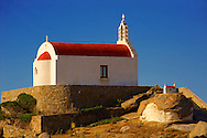 One of the hundreds of traditional  red roofed chapels on Mykonos with a plane landing, Cyclades Islads, Greece .<br /> <br /> Visit our GREEK HISTORIC PLACES PHOTO COLLECTIONS for more photos to download or buy as wall art prints https://funkystock.photoshelter.com/gallery-collection/Pictures-Images-of-Greece-Photos-of-Greek-Historic-Landmark-Sites/C0000w6e8OkknEb8