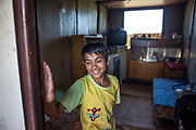 "The son of Juraj standing on the entrance of a container the family lifed in before they joined a pilot project constructing low-cost houses called ""From Shack into a 3E (Ecological and Energy Efficient) House"",<br /> which was implemented in the village of Rankovce located about 30 km from Kosicein 2013. The pilot project took place in a marginalized Roma community - all the builders were<br /> unemployed Roma living with their families in difficult conditions."