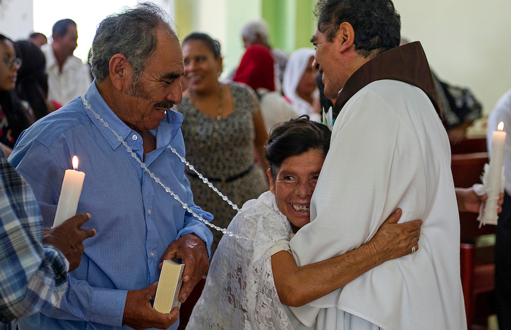 "In this July 23, 2016 photo, Francisca Santiago, 65, embraces the Rev. Domingo Garcia Martinez after he wed her and lifelong partner Pablo Ibarra, 75, in Santa Ana, in the Mexican state of Oaxaca. Santiago pulled in the priest for a big hug while a nose-wrinkling smile lit up her face. ""It was beautiful, everything I hoped for,"" Santiago said. ""Now we are together with the blessing of God."" NICK WAGNER / ASSOCIATED PRESS"