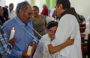 """In this July 23, 2016 photo, Francisca Santiago, 65, embraces the Rev. Domingo Garcia Martinez after he wed her and lifelong partner Pablo Ibarra, 75, in Santa Ana, in the Mexican state of Oaxaca. Santiago pulled in the priest for a big hug while a nose-wrinkling smile lit up her face. """"It was beautiful, everything I hoped for,"""" Santiago said. """"Now we are together with the blessing of God."""" NICK WAGNER / ASSOCIATED PRESS"""