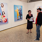 VENICE, ITALY - JUNE 01:  Artist Giuseppe Veneziano is interviewed in front of three of his works by Franca Urbani at Galleria Contini on June 1, 2011 in Venice, Italy. Veneziano's controversial paintings portray  pop culture icons and historical figures.
