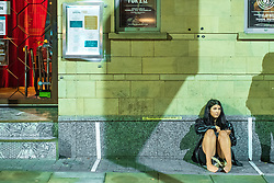© Licensed to London News Pictures. 10/10/2020. Manchester, UK. A woman sits on the ground outside a bar on Peter Street , after venues close . People out in pubs, bars and restaurants in Manchester City Centre ahead of the currently imposed daily 10pm curfew . Millions of people across the north of England are waiting to learn if the British Government will impose a regional lockdown on Monday (12th October 2020), as Coronovirus infection rates continue to rise rapidly . Photo credit: Joel Goodman/LNP