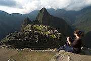 Machu Picchu Inca Ruins, young woman tourist looking down onto ruins, Mount Huayna Picchu in background, Sacred Urubamba Valley, Andes, Peru, sacred, temple, andean, mountain. .South America....