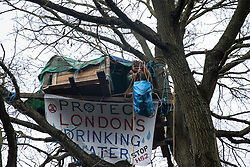 Harefield, UK. 3 February, 2020. An activist hauls up supplies to a treehouse high up in a tree at the woodland camp section of Harvil Road wildlife protection camp. Environmental activists from Save Colne Valley and Extinction Rebellion are seeking to prevent construction works for the HS2 high-speed rail link in the Colne Valley which would require the felling of hundreds of mature trees.