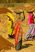 Women breaking up and carrying rocks at a construction site, Udaipur, Rajasthan, India