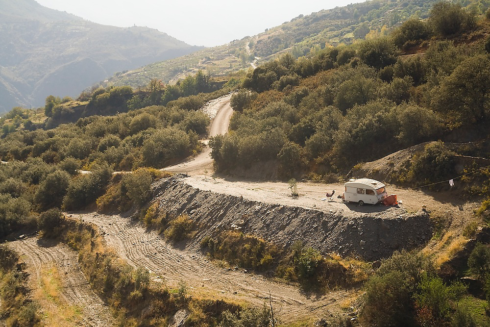 A traveler relaxes by her camper parked on a dirt road below the town of Pitres in Las Alpujarras, Andalusia, Spain.