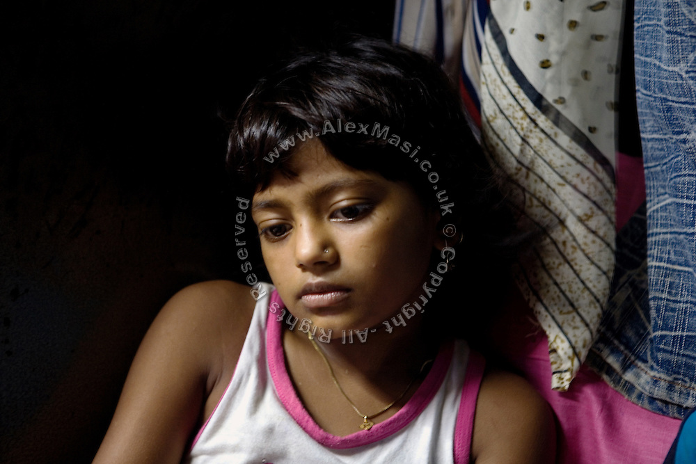A melancholic Rubina Ali, 9, the child actor playing the role of 'young Latika', the friend/lover of Jamal, protagonist of Slumdog Millionaire, the famous movie winner of 8 Oscar Academy Awards in December 2008, is portrayed inside her uncle's house in the slum where she still lives with her family next to the train station of Bandra (East), Mumbai, India. Various promises were made to lift the two young actors (Azharuddin Ismail and Rubina Ali) from poverty and slum-life but as of the end of May 2009 anything is yet to happen. Rubina's house was recently demolished with no notice as it lay on land owned by the Maharashtra train authorities and she is now permanently living with her uncle's family in a home a stone-throw away in the same slum. Azharuddin's home too was demolished in the past two weeks, as it happens every year in his case, because the concrete walls were preventing local authorities to clear a drain passing right behind it. As usual, his father is looking into restoring the walls as soon as the work on the drain has been completed.