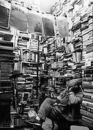 Ceiling high bookshelves filled with a mess of books surround the napping shop owner, Ba Trieu street, Hanoi, Vietnam, Southeast Asia