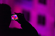 Silhouettes of people using mobile phones to photograph Vivid Festival, Sydney, Australia