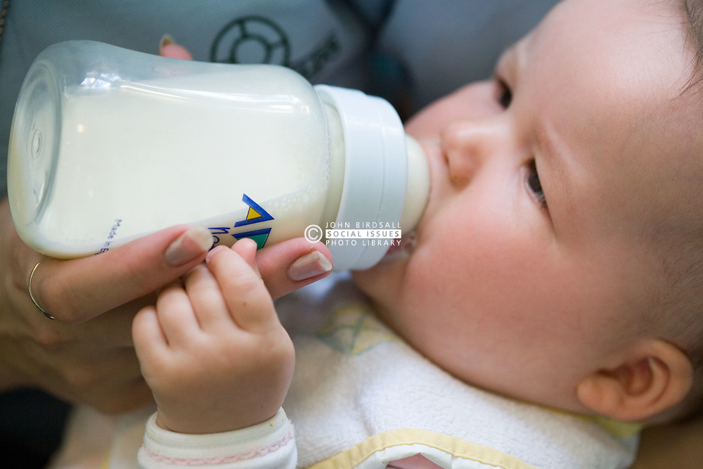 Baby at Nursery School; drinking from a bottle,