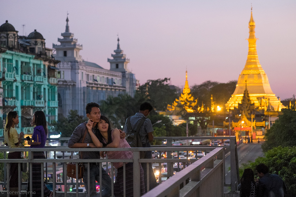 A young couple enjoying the city view from a bridge near the famous Sule Pagoda of Yangon, Myanmar. <br /> Photo by Lorenz Berna