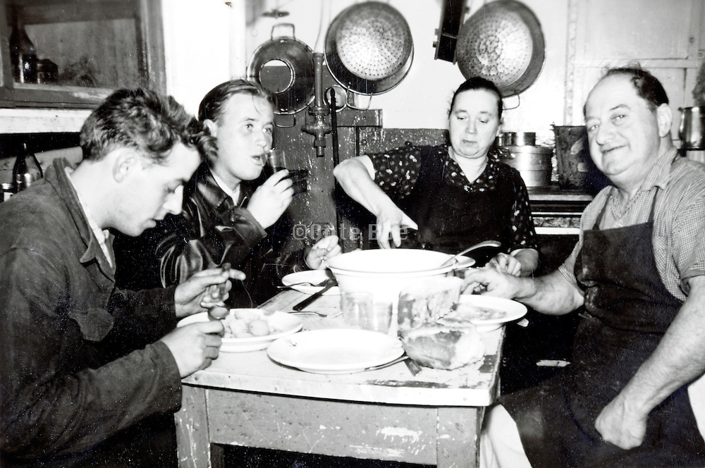 rural family sitting eating in the kitchen on a very small table France 1940s