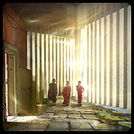 Three child monks stroll away along a heavy stone path past a door and columns of concrete and light surrounded by swirls of light, the spiritual aura emerging from their connectedness.
