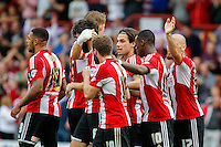 Brentford FC's Jota celebrates with his team mates after scoring the first goal during the Sky Bet Championship game against Leeds United at Griffin Park