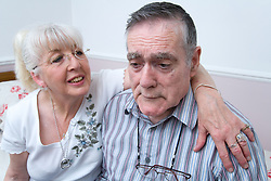Woman with her arm around husband with Alzheimer's Disease comforting him,