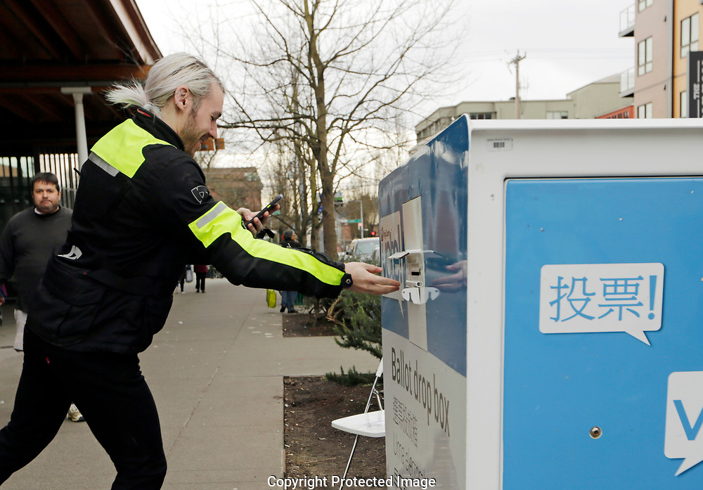 Todd Meagerle records himself as he drops off his ballot in the Washington State primary, Tuesday, March 10, 2020 in Seattle. Washington is a vote by mail state. (AP Photo/John Froschauer)
