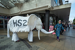 """© Licensed to London News Pictures. 02/09/2021. LONDON, UK.  A climate activist from Extinction Rebellion with a pantomime white elephant at a protest in the town centre of Uxbridge, which is in Boris Johnson's home constituency, against HS2 (High Speed Rail 2) to highlight the negative ecological effects of the new rail network.  The event takes place on day eleven of the two week 'Impossible Rebellion' protest to """"target the root cause of the climate and ecological crisis"""".  Photo credit: Stephen Chung/LNP"""