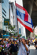 """20 DECEMBER 2013 - BANGKOK, THAILAND:  An anti-government protestor carries a Thai flag down Silom Road in Bangkok. Thousands of anti-government protestors, supporters of the so called Peoples Democratic Reform Committee (PRDC), jammed the Silom area, the """"Wall Street"""" of Bangkok, Friday as a part of the ongoing protests against the caretaker government of Yingluck Shinawatra. Yingluck dissolved the Thai Parliament earlier this month and called for national elections on Feb. 2, 2014. The protestors want the elections postponed and the caretaker government to step down. The Thai election commission ruled Friday that the election would go on dispite the protests.         PHOTO BY JACK KURTZ"""