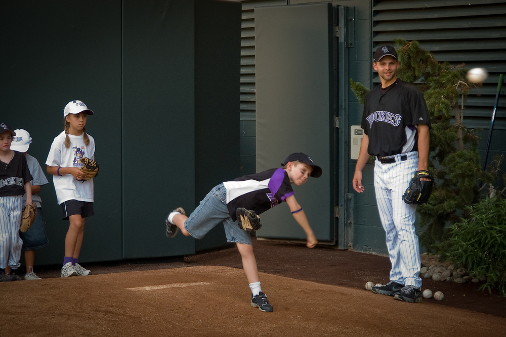 Eight year-old LUKE DAVIS of Littleton, Colorado pitches while TAYLOR BUCHHOLZ. pitcher for the Colorado Rockies watches.