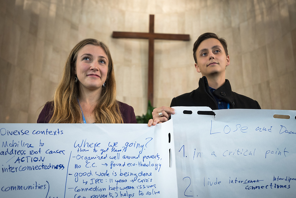 1 December 2019, Madrid, Spain: Lutheran World Federation delegates Erik Bohm from Church of Sweden (right) and Erika Rodning from the Evangelical Lutheran Church in Canada (left) hold sheets of paper on which key discussion points have been summarized, as representatives of various faiths gather in the Iglesia de Jesús (Church of Christ) of the Iglesia Evangélica Española (Evangelical Church of Spain) for an interfaith dialogue and prayer service on the eve of the United Nations climate conference (COP25) in Madrid, Spain.