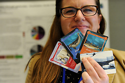 May 10, 2017 - Fairbanks, AK, U.S. - Jessica Brunacini shows cards from the ECOCAINS Arctic Life food web card game at the Polar Partnership booth at the Arctic Council meeting in Fairbanks, Alaska, on Wednesday, May 10, 2017. The card game produced with A National Science Foundation grant teaches players about the arctic food web and ice and the effects of climate change. (Credit Image: © Bob Hallinen/Alaska Dispatch News via ZUMA Wire)