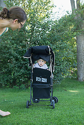 Baby boy sitting in pram and looking to his mother, Munich, Bavaria, Germany
