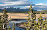Storm clouds hover above Hayden Valley, Mt. Washburn, and the Yellowstone River  at sunset in Yellowstone National Park.