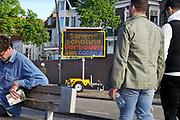 Nederland, Nijmegen, 25-4-2020 Een elektronisch mededelingenbord van de gemeente herinnert de mensen eraan voldoende afstand te houden, en dat het verboden is een samenscholing te hebben .  op de waalkade . Foto: Flip Franssen