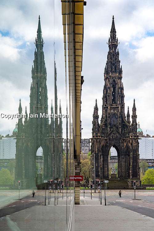 Edinburgh, Scotland, UK. 1 May 2020. Views of Edinburgh as coronavirus lockdown continues in Scotland. Streets remain deserted and shops and restaurants closed and many boarded up. Pictured; Scott Monument and deserted streets reflected in window. Iain Masterton/Alamy Live News