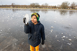 © Licensed to London News Pictures. 13/02/2021. London, UK. A young boy looks at a lump of ice on Rushmere Pond on Wimbledon Common in South West London which has frozen over as freezing temperatures once again hit the South East. This week the government will mull over its road map for unlocking the country from Covid-19 restrictions as the vaccination programme starts to take effect. Photo credit: Alex Lentati/LNP<br /> *Permission Granted*