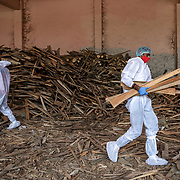 New Delhi 28 April 2021 <br /> <br /> Relatives in PPE suits collect fire wood for cremating their family members  at the Gazhipur cremation ground in New Delhi.