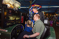 Kids of all ages have rainy day fun at the Half Moon Arcades Wednesday afternoon.  Brian Healey with Isabelle Bird as co-pilot take on a game of Blazing Angels with Mark Healy looking on.  (Karen Bobotas/for the Laconia Daily Sun)